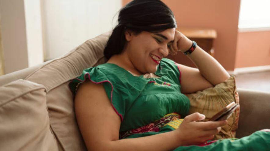 une Hijra heureuse sur un canapé
